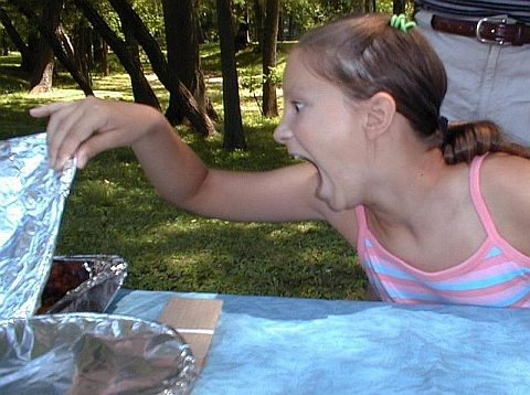 Mädchen erschrickt beim Blick in die Alu-Schale