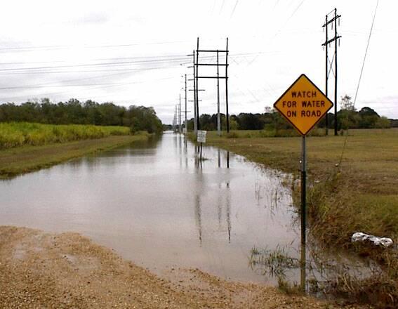 Straße mit Warnschild steht unter Wasser.